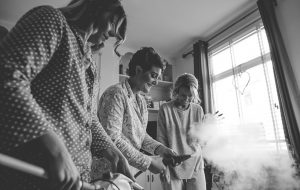 Black and white photo of bridesmaids trying to steam wedding dress