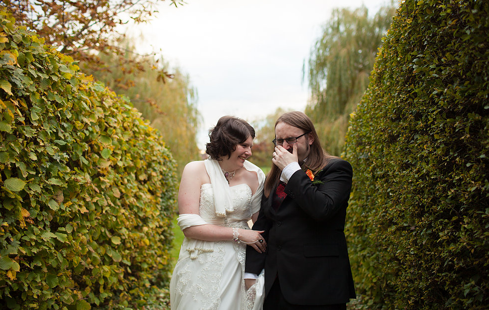 Bride and groom laughing stood between two hedges
