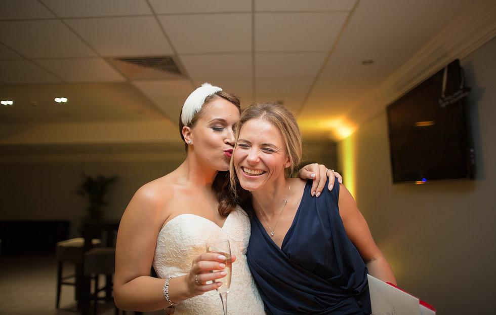 Bride kisses laughing best friend