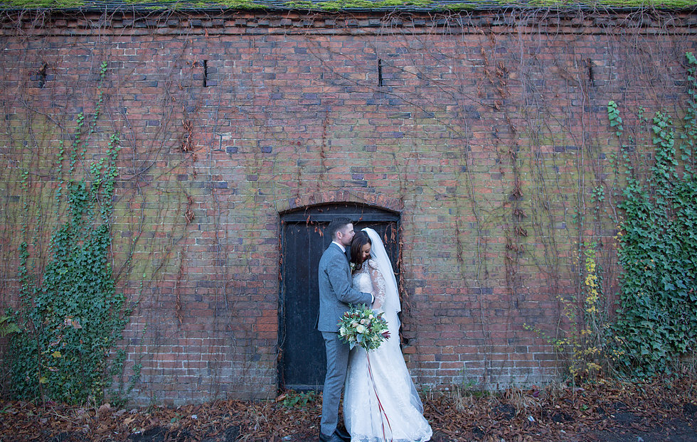 Bride in Maggie Sottero gown stood with husband