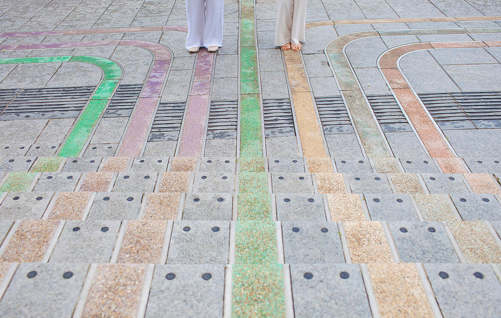Two brides stood at bottom of steps, coloured lines leading to them