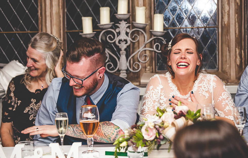 Bride and groom laughing during speeches at Weston Hall in Staffordshire