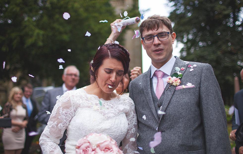 Bride getting confetti in her mouth