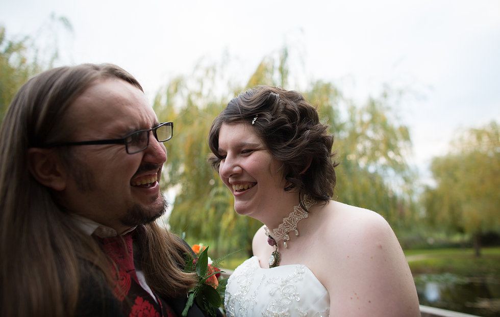 Groom with long hair laughing with his wife