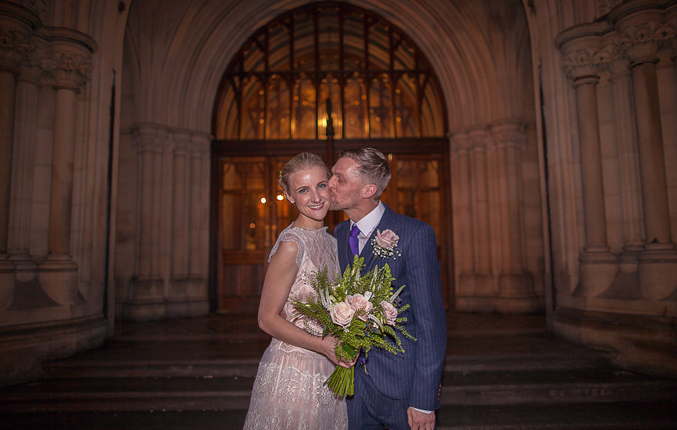 Groom kissing bride on cheek outside Manchester Town Hall