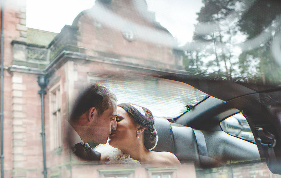 Photo of couple in the back of a wedding car taken in rear view mirror